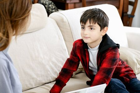 engaged child listens to the mother who tells him a story in home setting