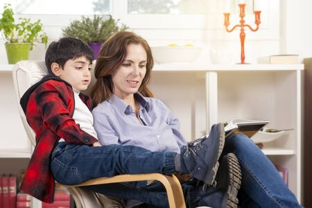 mother reads a storybook to her child ditting in his living room