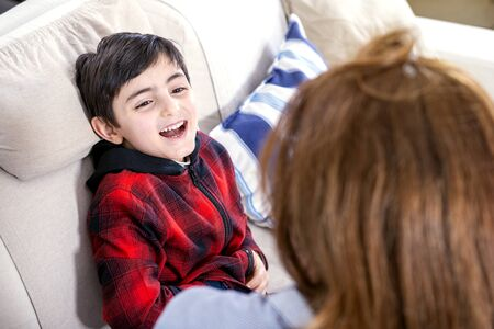 smiling child plays with his mother on the sofa at home Banque d'images