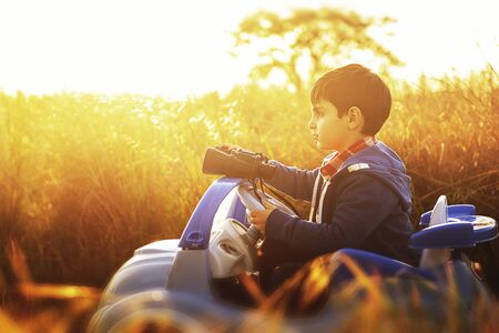 serious look of a child in the middle of the countryside, sitting on his toy car at sunset
