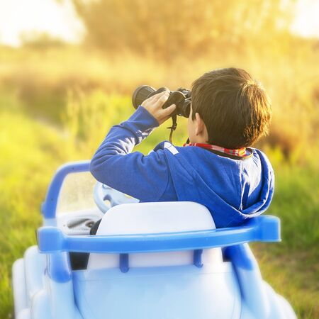 young boy ventures out into the world with his toy car, in a rural setting at sunset