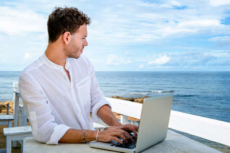 handsome and successful caucasian man working with a laptop on the beach. freelance and remote work. student on the mediterranean shore