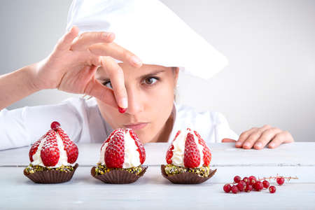 woman pastry chef decorates small strawberry cakes