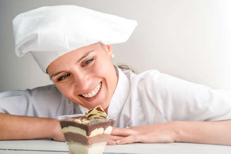 woman pastry chef smiling while observing tiramisu, a typical sweet of Sicilian pastry