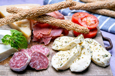 typical italian starter with salami, cold cut parmesan mozzarella and parma ham on a cutting board Banque d'images