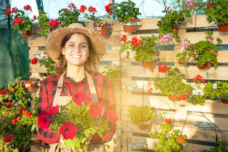 beautiful smiling gardener in a flower shop offers a spring plant Banque d'images