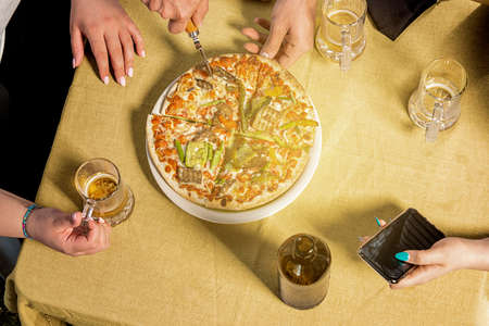 cutting vegetarian pizza on the table shared with friends. free time celebrating with Italian food