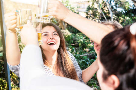 group of people toasting happy smiling with beer outdoors Banque d'images