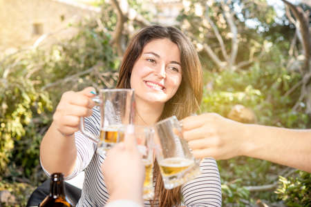 group of people toasting with beer outdoors
