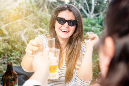 happy young woman with sunglasses smiles and toasts enjoying friends in the open air sitting at restaurant Banque d'images