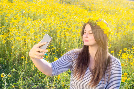 beautiful curvy woman poses outdoors with daisy crown. take selfie in a meadow with daisies