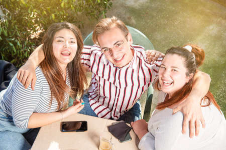 three friends smile outdoors ready to celebrate