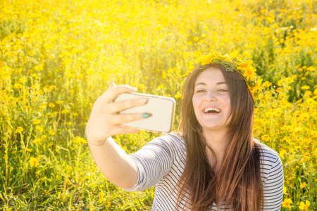 beautiful and nice girl laughs while taking a self-portrait with a mobile phone