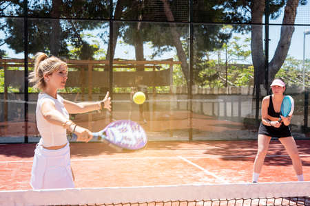 woman smashing in paddle tennis action. Training Basket balls in the foreground