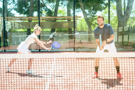 mixed couple plays on a padel court outdoor in a sunny summer day
