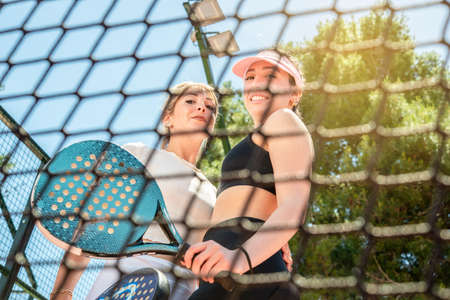 two smiling girls behind a tennis net pose after a game Banque d'images