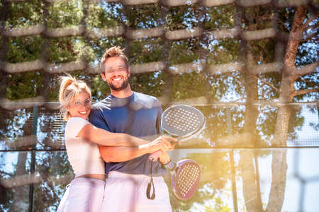 man and a woman happily hug each other after a game of padel