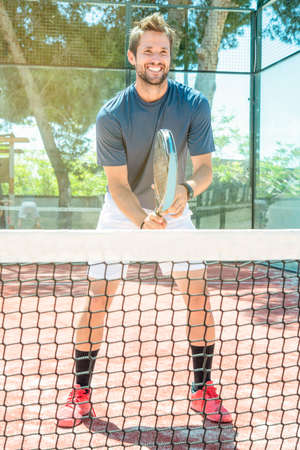 happy smiling young man plays tennis on an open air court