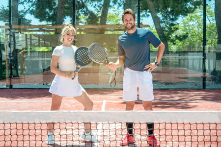mixed couple smiles after the game on an outdoor tennis court Banque d'images