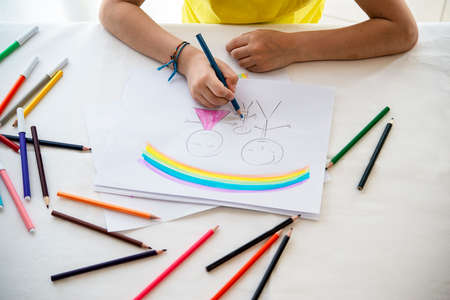Hands of a child while drawing a concept of family father mother son parents with pencils
