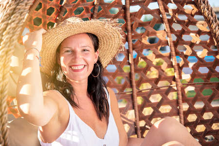 smiling pretty woman with hat having free time at beach Reklamní fotografie