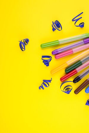 markers of different colors with a white Notepad on a yellow background, top view. colorful pens with close-up paper decorations Stockfoto