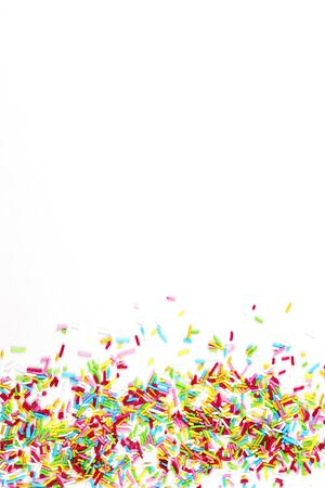 culinary pastry rainbow sprinkles are scattered on a white background. small sugar sprinkles for decorating cakes