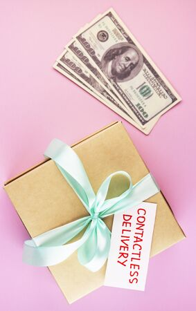 gift box with text contactless delivery and money top view. image of a secure courier delivery on a pink background. Stockfoto
