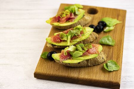 sandwiches of fresh avocado and red fish on a wooden tray, top view. vegetarian low-calorie food for weight loss from fresh vegetables