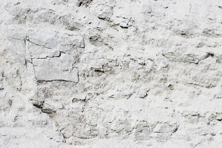 abstract texture of coastal white stone for background, close-up. rough, uneven surface of the rock pebbles