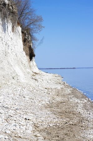 steep rocky Bank of a large river. slope of white stones on the beach