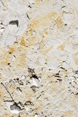 abstract texture of coastal white stone with red stripes for background, close-up. rough, uneven surface of the rock pebbles