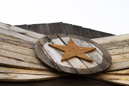 vintage red wooden star in the center of the circle, side view. wood construction with an asterisk in the center