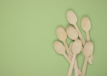 Eco-friendly disposable tableware made of bamboo wood and paper on a green background. Draped spoons scattered on the table. The concept of zero waste. Preserving the purity of nature