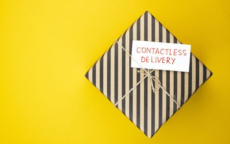 The box is delivered by contactless delivery on an orange background. the package is ordered online during the global covid-19 coronavirus pandemic. food delivery to your home