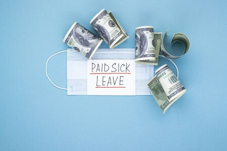 Medical mask with dollars and the words paid sick leave on a blue background. Concept of economic dependence on the COVID-19 coronavirus pandemic