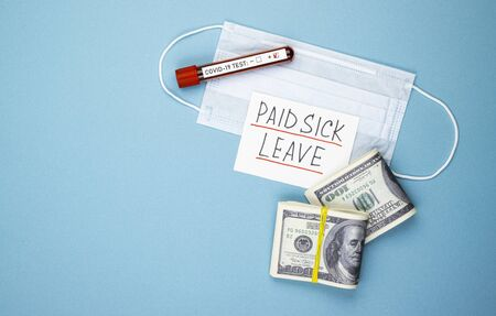 paid sick leave with a medical mask and money on a blue background. dollars in a pack and a positive test for covid-19
