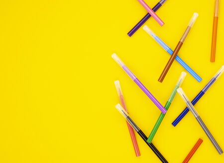 colorful markers are scattered on a yellow background. educational school supplies. stationery for the office. back to school. online learning