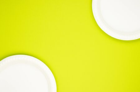 Eco-friendly biodegradable paper plates on a green background. preserving the purity of nature. the rejection of the plastic