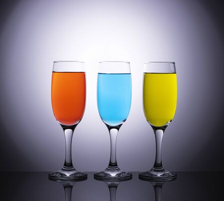 Colored wines in champagne glasses on a beautiful diffuse background. Creative shooting of alcoholic beverages and glassware