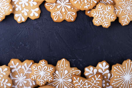 gingerbread snowflakes on a black background, top view. new year gingerbread background with space for text