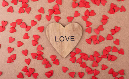 Wooden heart with the inscription love with small scattered red hearts on a brown background. Valentine's day, mother's day