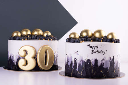 Festive black and white cakes 30 years old with golden balls and dark berries. birthday and anniversary cake