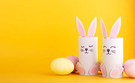 cute Easter bunnies made of paper with colorful Easter eggs. happy easter background