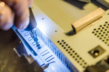 man unspins the cover of the computer of the monoblock with a screwdriver with backlight