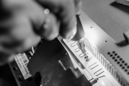 man unspins the cover of the computer monoblock with a screwdriver with backlight black and white Stockfoto