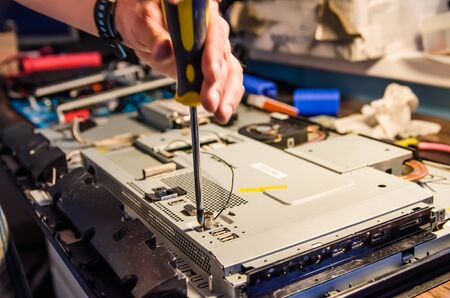 Technical support worker unspins the cover of the computer monoblock with a screwdriver