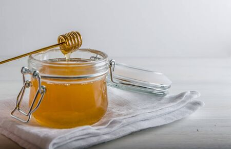 fresh honey drains from spoonfuls for honey with a copy space Reklamní fotografie