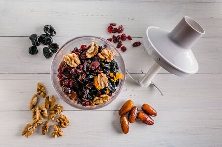 ingredients for energy balls in a blender on white background with copy space