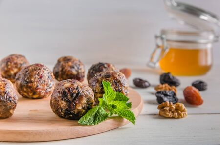 vegetarian food, homemade energy balls of walnuts, dates, prunes, cranberries and honey on white background with copy space